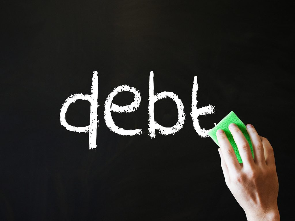 debt spelled out in lower case lettrers with white chalk on a blackboard