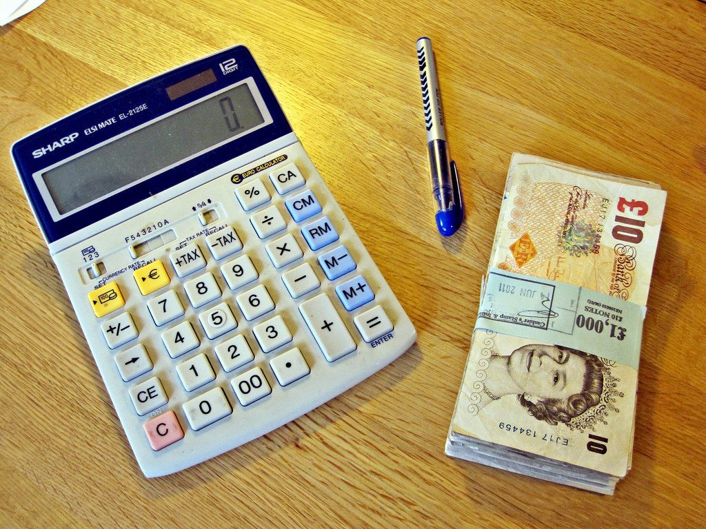 Calculator on table next to a wad of english bank notes