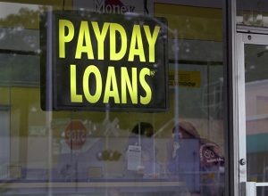 yellow on black payday loan sign in a shop window